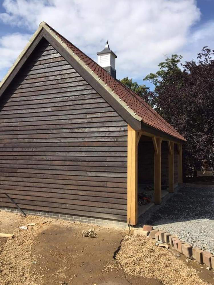 A timber frame building cladded with ebonised oak feather edge cladding